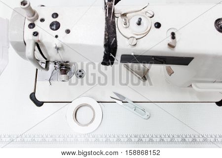 Sewing machine with tools top view, free space. Seamstress workplace with metre and scissors. Professional sewing equipment, tailor workspace, fashion concept