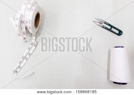 Tailor workplace top view, free space. Metre, string bobbin and scissors on white background. Sewing supplies frame