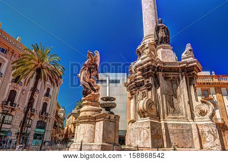 The obelisk-like Colonna dell Immacolata, Immaculate Virgin with palm tree in the square San Domenico in Palermo, Sicily, Italy.