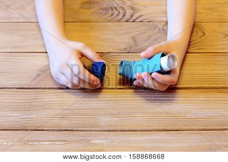 Small child holds asthma inhaler in his hands. Inhalation treatment of respiratory diseases. Allergy and bronchial asthma concept. Old wooden background