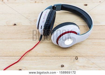 White Headphones on the wood desk background.