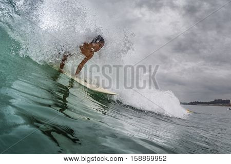 BALI, CANGGU - NOVEMBER 25 2016: Young surfer catching the wave in the ocean