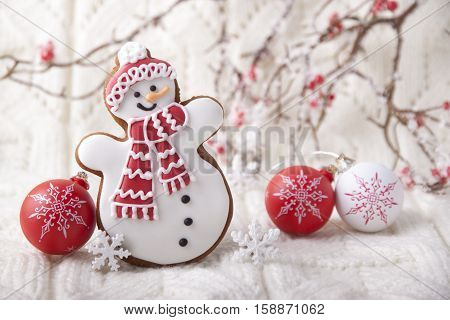 Christmas background with gingerbread in the form a snowman on a white knit fabric.