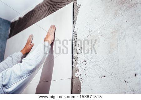 Industrial Worker, Handyman Installing Big Ceramic Tiles On Bathroom Walls. Shower Area Covered In C