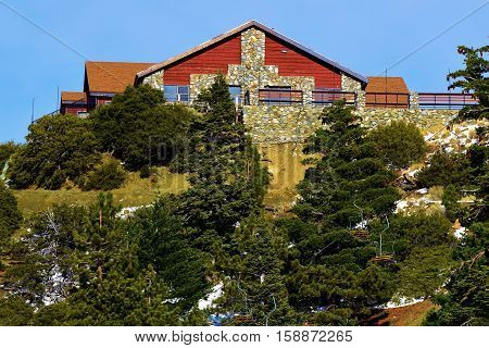 Rustic mountain lodge on top of a slope surrounded by a Pine Forest taken in Mt Baldy, CA