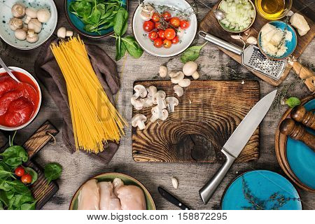 Raw Italian spaghetti and ingredients for cooking pasta on a wooden table top view