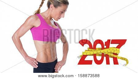 Female bodybuilder posing in pink sports bra against digital image of 3D new year with tape measure