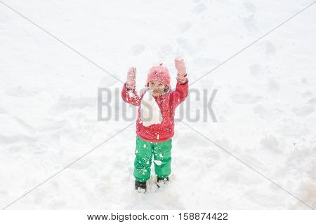 Playful girl with braids playing in snow throwing it in the air having fun and being active. Natural lifestyle and free childhood concept with copy space.