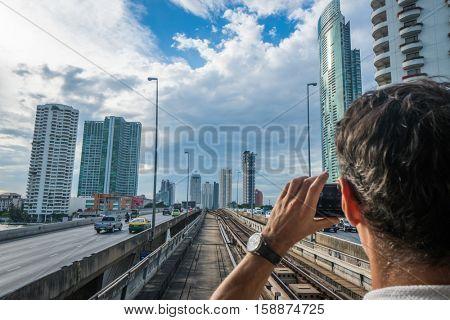 Back view of tourist man using mobile phone to do photo of Bangkok panorama