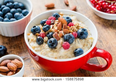 Porridge bowl oats with blueberries, raspberry, almonds and granola. Healthy breakfast, diet, well-being concept. Close up view