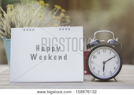 happy weekend note on morning sunlight with alarm clock
