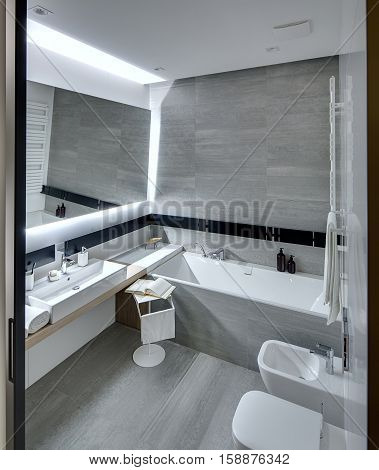 Bathroom in a modern style tiled with the white and gray tiles. There is a white sink with accessories, mirror, bath, towel holder, towel radiator, toilet and a bide, stand with a towel and a book.