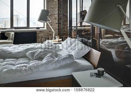 Loft style bedroom with brick wall. There is a bed with pillows, lamps with lampshades, wardrobe with glass sliding doors, tables with a cup and a book, armchair, black radiator. Horizontal.