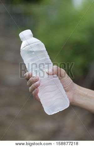 woman holding a bottle of water after fitness