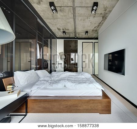 Hall in a loft style with white walls and concrete ceiling. There is a TV, bed with pillows, lamps with lampshades, wardrobe with glass sliding doors, tables, parquet with a carpet on the floor.