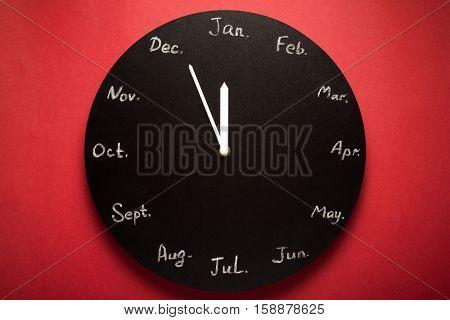 Black round clock calendar. 12 months. Red background