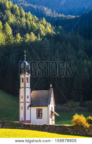 The church of Santa Maddalena. Tirol, Dolomites. Rocky peaks and forested mountains surrounded by green Alpine meadows. Sunny warm autumn day