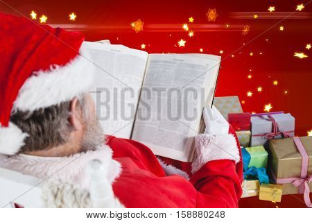Santa claus reading bible with christmas present beside him against bright star pattern on red