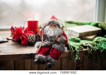 Santa sitting on a wooden window sill, decorated with Christmas trinkets. Wooden window sills reader rug and books.The concept of Christmas