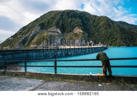 Industrial worker man carries repair maintenance work using arc welding on metal construction on the Enguri hydroelectric dam HES next to Jvari Reservoir with beautiful turquoise water against the mount Upper Svaneti Georgia