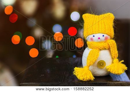 snowman wearing a knitted yellow hat and scarf. Behind him blurred Christmas lights background. The concept of the winter holidays