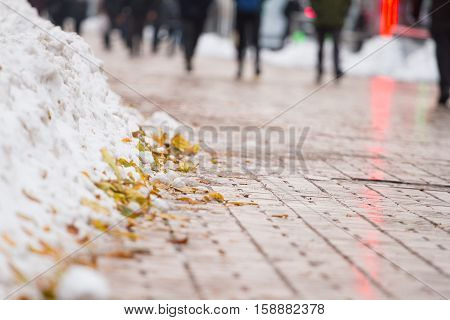 Part of winter frost sidewalk. Pile of collected snow and autumn leaves. Cold city street