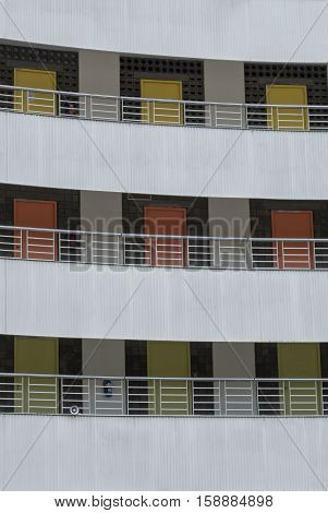 Building facade with external gangways with different coloured apartment entrance doors in each of 3 levels.