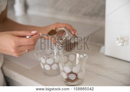 Hand with full spoon and glasses preparing instant coffee