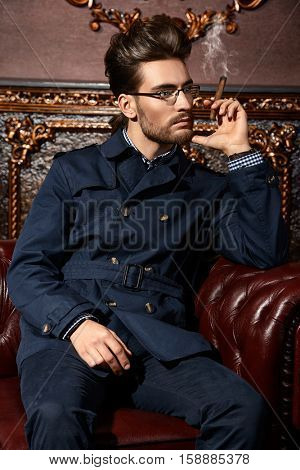 Portrait of a well-dressed imposing man in elegant glasses posing in apartments with luxurious classic interior. Men's beauty, fashion. Hair styling, barbershop.