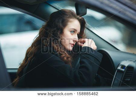 Sad young woman driving car in rain