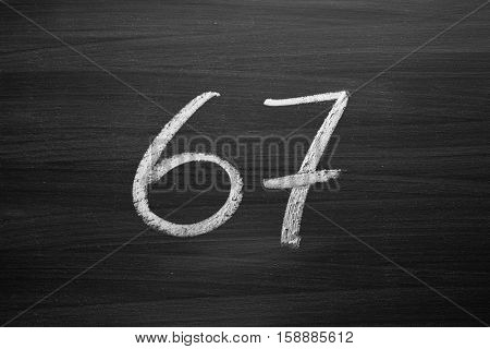 number sixty seven enumeration written with a chalk on the blackboard