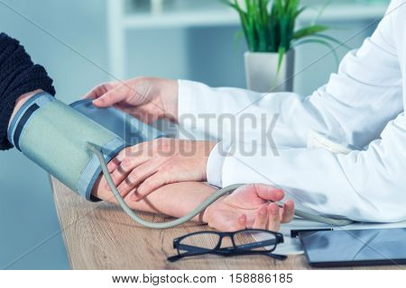 Doctor cardiologist measuring blood pressure of female patient in hospital office health care control and monitoring