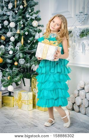 Pretty eight year old girl in a beautiful festive dress standing in a Christmas room and holding a gift. Luxurious Christmas decoration. Beauty, children fashion.