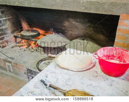 Picture of the stone bread oven stove with burning wood fire and red flames inside. lurred image of the red pot on the table with water-logged dough.