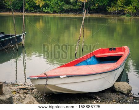 Picture of the landscape scene in the forest. With fishing boat on the near river-bank and depths of a green forest on the far bank. Boat with red top laying on the stony shore of the river.