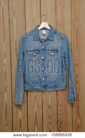 A blue denim jean shirt is on clothes-hanger on wooden background