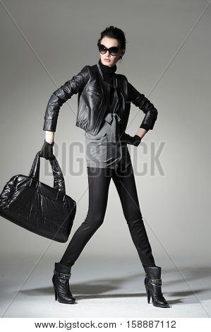 full-length fashion girl in sunglasses with handbag posing on light background