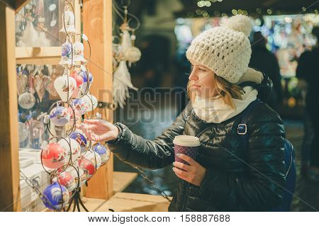 Young beautiful woman looking for presents at christmas market. Winter holidays souvenir shop