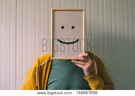 Put a happy face on happiness and cheerful emotions concept man holding picture frame with smiley emoticon printed