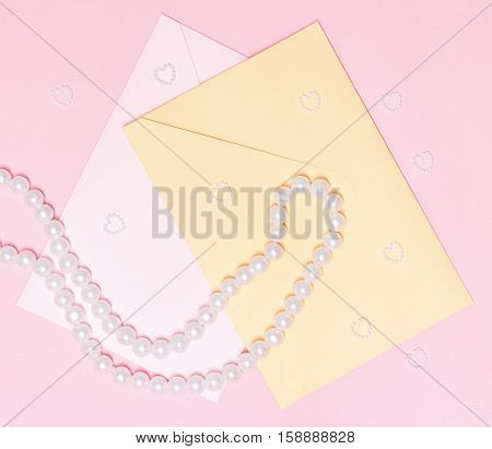 Close-up of two envelopes with pearl chaplet and small hearts made of beads on pink textured background. Love letters, wedding invitations