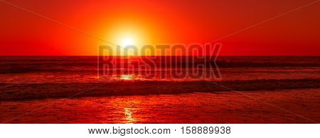 Setting sun over the Pacific ocean colors the sky and waves in red color.