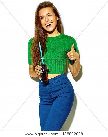 portrait of beautiful happy cute brunette woman model in casual green hipster summer clothes with no makeup isolated on white in sunglasses drinking cola from bottle with straw