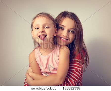 Happy smiling mother hugging with love her frolic grimacing kid showing the tongue. Toned closeup portrait poster