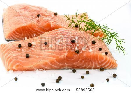 Patches of fresh salmon marinated with sea salt pepper and dill isolated on a white background