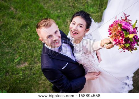High angle portrait of cheerful wedding couple standing on grassy field