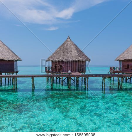 Overwater bungalows with stair descending into the sea. Turquoise color of the lagoon. Tropical island in the Indian Ocean. Luxury holiday.