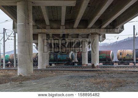 Railway cisterns under the bridge. Big concrete overpass.
