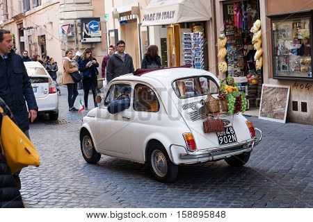 Rome Italy - November 27 2016: An old white car of the '70s a symbol of Made in Italy the legendary Fiat 500 in the alleys of Rome.