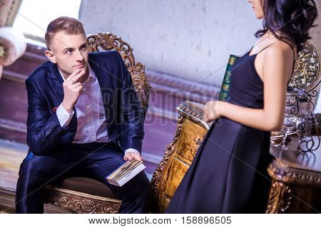 Loving mid adult man in suit looking at woman while sitting on chair
