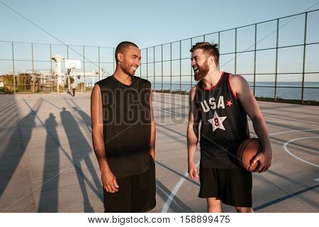 Two happy smiling sportsmen talking to each other while standing at the playground